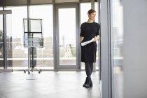 Donna d'affari in piedi in ufficio guardando fuori dalla finestra — Foto stock