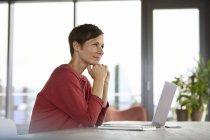 Улыбающаяся женщина сидит за столом дома с помощью ноутбука — стоковое фото