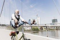 Giocoso uomo maturo in bicicletta sul ponte in città — Foto stock