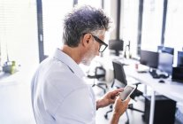 Homme d'affaires mature au bureau en utilisant un smartphone — Photo de stock