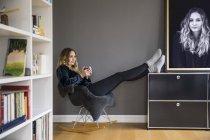 Zufriedene junge Frau entspannt bei Heißgetränk zu Hause — Stockfoto