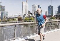 Улыбающийся взрослый мужчина с наушниками, работающими на мосту в городе — стоковое фото