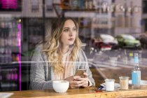 Portrait of pensive young woman in a coffee shop looking through window — Stock Photo