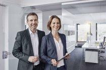Портрет улыбающегося бизнесмена и деловой женщины с планшетом в офисе — стоковое фото
