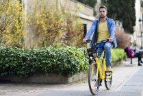 Giovane uomo in bicicletta a noleggio in città — Foto stock
