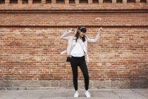 Mulher feliz com telefone celular ouvindo música em fones de ouvido contra parede de tijolo — Fotografia de Stock