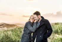 Happy couple in dunes at sunset — Stock Photo