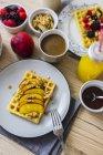 Стол для завтрака с вафельной гарой с нектарином, грецкими орехами и кленовым сирапом — стоковое фото