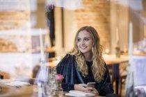 Портрет улыбающейся молодой женщины, ожидающей в ресторане — стоковое фото