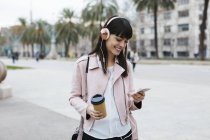 Spain, Barcelona, smiling woman with coffee, cell phone and headphones in city — Stock Photo