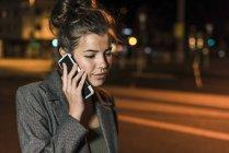 Junge Frau telefoniert nachts — Stockfoto