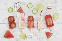Homemade watermelon and coconut cream ice lollies with lime and cucumber slices, fresh coconut chips on ice cubes — стоковое фото