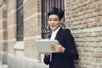 Portrait of content young businesswoman using tablet outdoors — Stock Photo