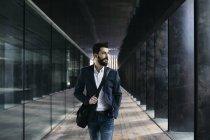 Businessman walking along arcade — Stock Photo