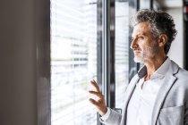Retrato de empresário maduro confiante olhando pela janela — Fotografia de Stock
