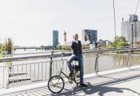 Happy mature man with bicycle listening to music on bridge in the city — Stock Photo