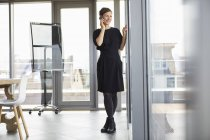 Mujer de negocios sonriente en la oficina en el teléfono celular - foto de stock