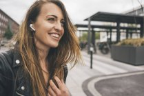 Sorridente giovane donna che indossa telefoni in-ear — Foto stock