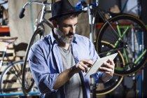 Людина в майстерні велосипеда за допомогою планшета — Stock Photo