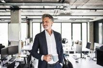 Усміхнений зрілий бізнесмен з кавовою кухлем ходьба в офісі — стокове фото