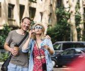 Щаслива пара з кавою піти дме мильні бульбашки в місті — стокове фото