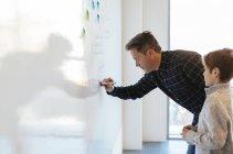 Бізнесмен в офісі письмовій формі на дошці з сином дивляться — стокове фото