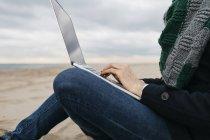 Geschäftsmann sitzt im Winter am Strand und benutzt Laptop, Teilsicht — Stockfoto