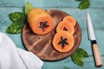 Papaya en rodajas sobre tabla de cortar - foto de stock