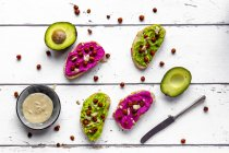 Baguette with guacomole and beetroot hummus, roasted chick peas and tahin dressing — Stock Photo