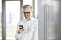 Smiling businessman at the window looking on cell phone — Stock Photo