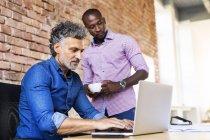 Collega guardando uomo d'affari che lavora sul computer portatile in ufficio — Foto stock