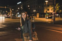 Portrait of young businesswoman with baggage and cell phone at night — Stock Photo