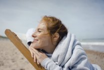 Smiling woman lying in deck chair, enjoying sunbath at the beach — Stock Photo