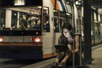 Портрет молодої жінки, яка очікує на трамвайну зупинку вночі за допомогою планшета — стокове фото