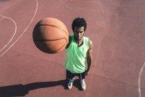 Молодой баскетболист держит мяч — стоковое фото