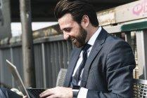 Felice uomo d'affari seduto all'aperto su una panchina utilizzando il computer portatile — Foto stock