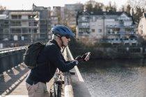 Старший человек со шлемом велосипедиста с помощью смартфона на мосту — стоковое фото