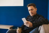 Businessman with takeaway coffee sitting and using cell phone — Stock Photo