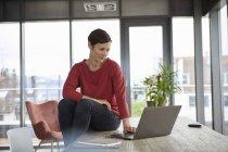 Улыбающаяся женщина сидит дома за столом с помощью ноутбука — стоковое фото