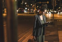 Young businesswoman with leather bag looking at cell phone by night — Stock Photo