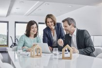 Business people having a meeting in office with laptop and architectural models — Stock Photo