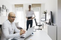 Man using laptop in home office with colleague moving past — Stock Photo