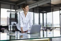 Businesswoman standing at glass table in office with laptop looking sideways — Stock Photo