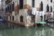 Italy, Venice, boat on canal and laundry at house — Stock Photo