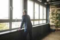 Maduro hombre de negocios de pie en la ventana en la oficina - foto de stock