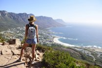 South Africa, Cape Town, woman standing looking at the coast during hiking trip to Lion's Head — Stock Photo