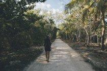 Cuba, Cienaga de Zapata, Jeune femme avec sac à dos marchant sur la rue bordée d'arbres — Photo de stock