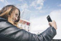 Sorridente giovane donna prendendo un selfie all'aperto — Foto stock