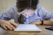 Primer plano de la mujer inclinándose sobre la tableta en el escritorio - foto de stock