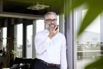 Smiling businessman standing at French door using cell phone — Stock Photo